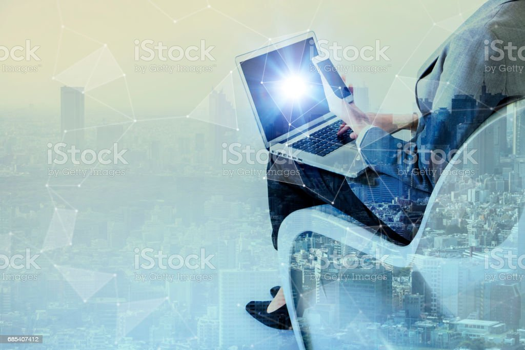 Double exposure of business persons holding tablet PC and modern cityscape, Internet of Things(IoT) conceptual abstract stock photo