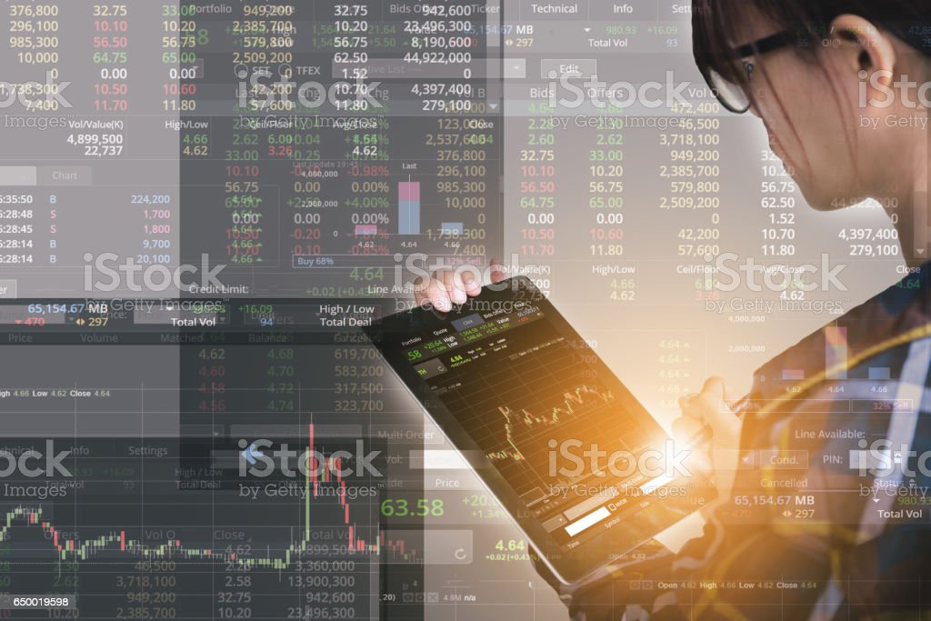Double exposure of business woman with glasses in hipster shirts holding tablet for check stock market graph with flare light, Business Trading concept stock photo