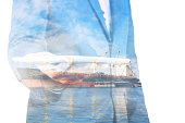Double exposure of businessman hand hold tablet, cargo port ship