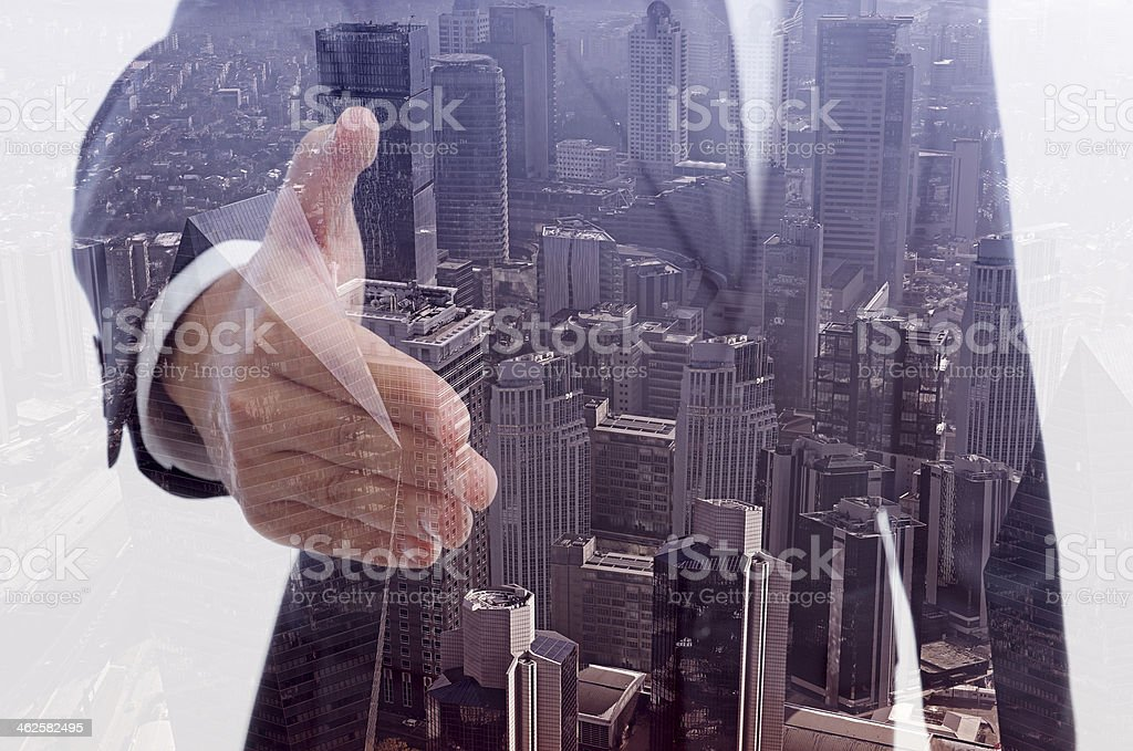 Double exposure of businessman offering handshake stock photo