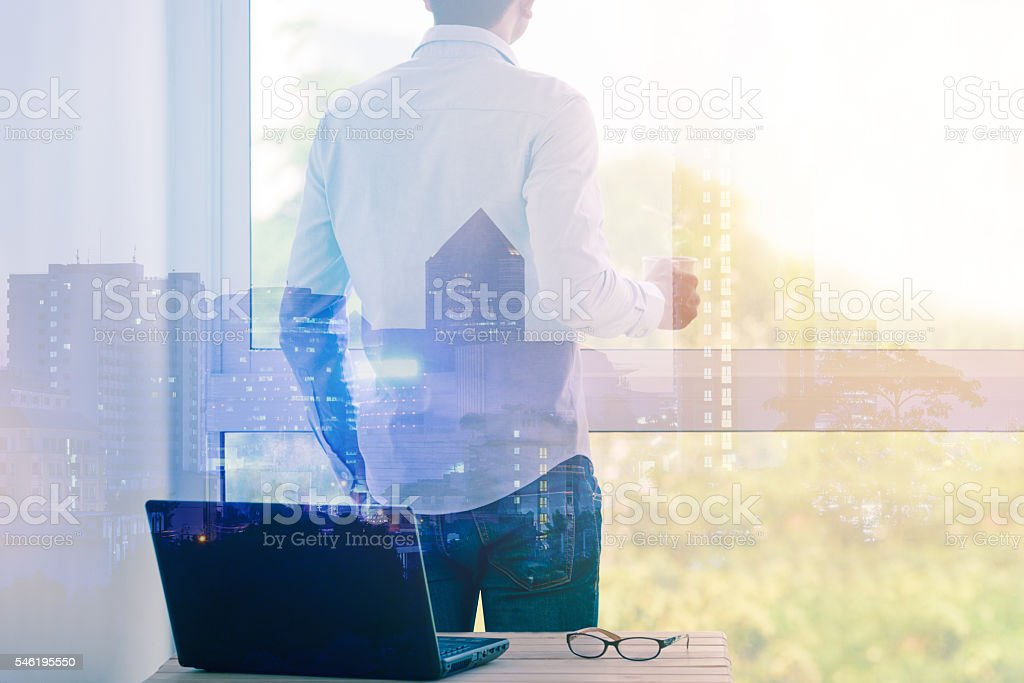 Double exposure of businessman relaxing with coffee by the window. stock photo