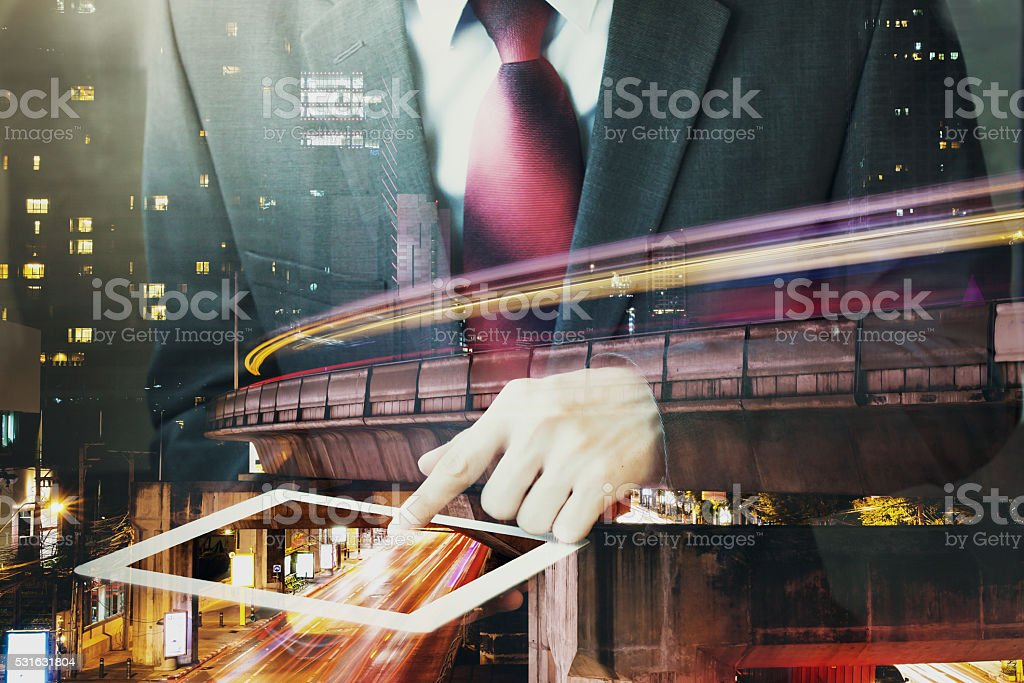 Double Exposure of Businessman touching a tablet in night cityscape stock photo