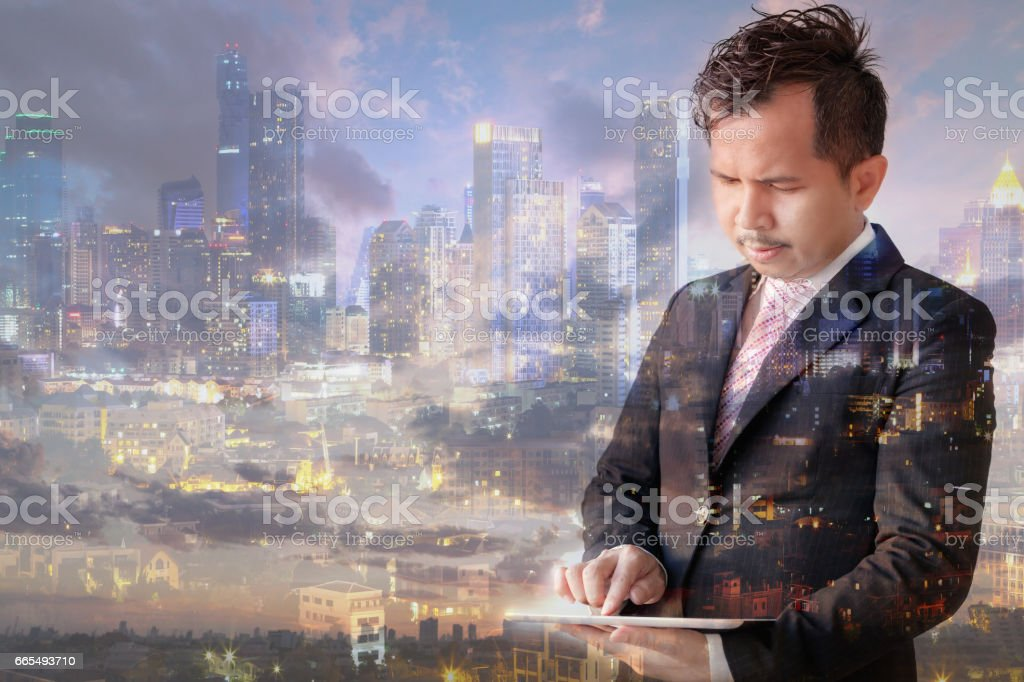 Double exposure of businessman touching digital tablet. stock photo