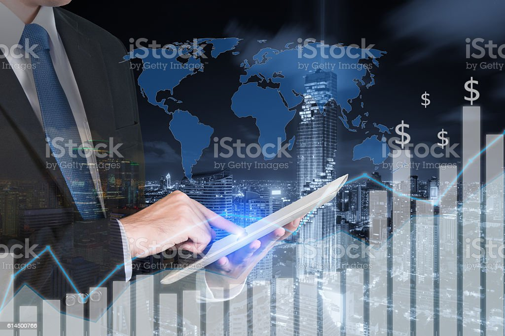 Double exposure of businessman using the tablet with city stock photo