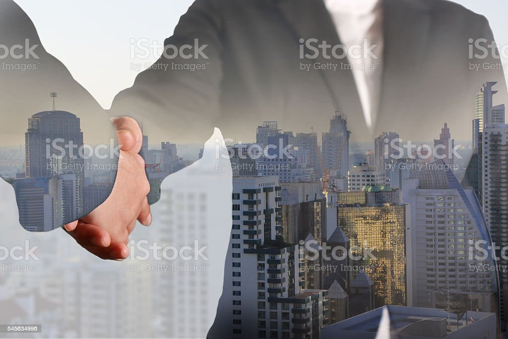Double exposure of Businesswomen handshaking and city in the morning. stock photo