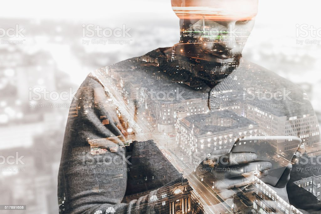 Double exposure of city and man using smart tablet stock photo
