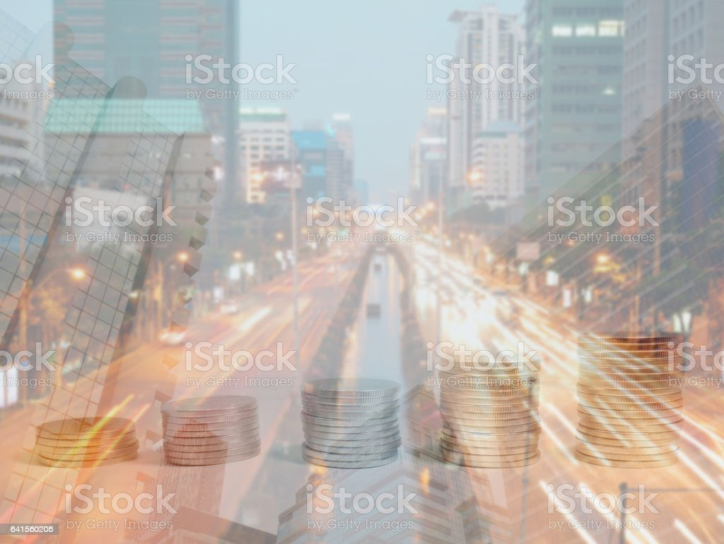 Double exposure of coins, buildings and road at dusk stock photo