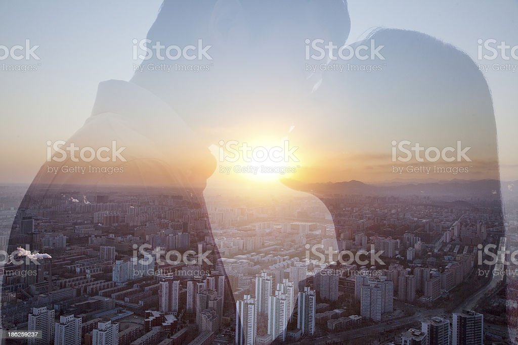 Double exposure of couple kissing over cityscape stock photo