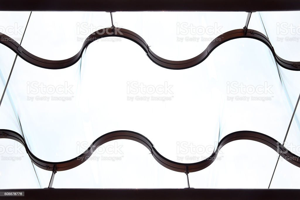 Double exposure of curvilinear metal curtain holder against window glass stock photo