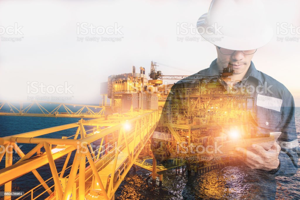 Double exposure of Engineer or Technician man with safety helmet operated platform or plant by using tablet with offshore oil and gas platform background for oil and gas business concept stock photo