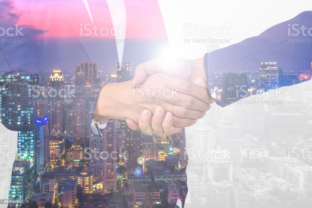 Double exposure of handshake and city stock photo