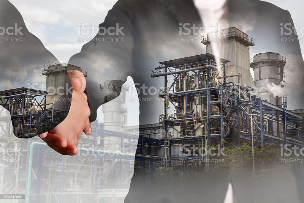 Double exposure of handshake and Power Reactor Factory stock photo