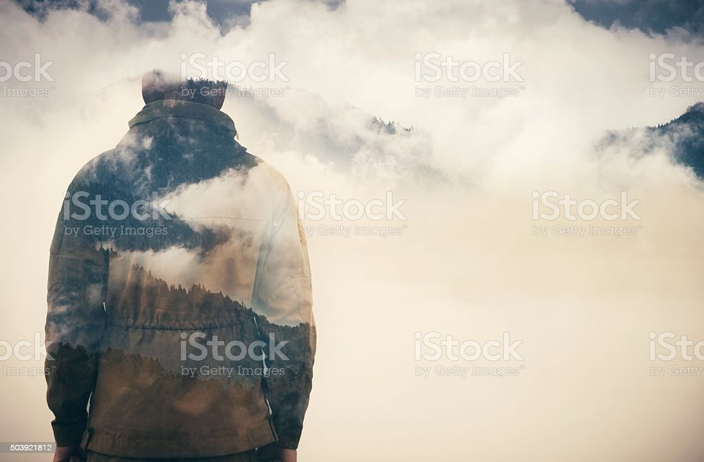 Double Exposure of Man and Cloudy Mountains stock photo
