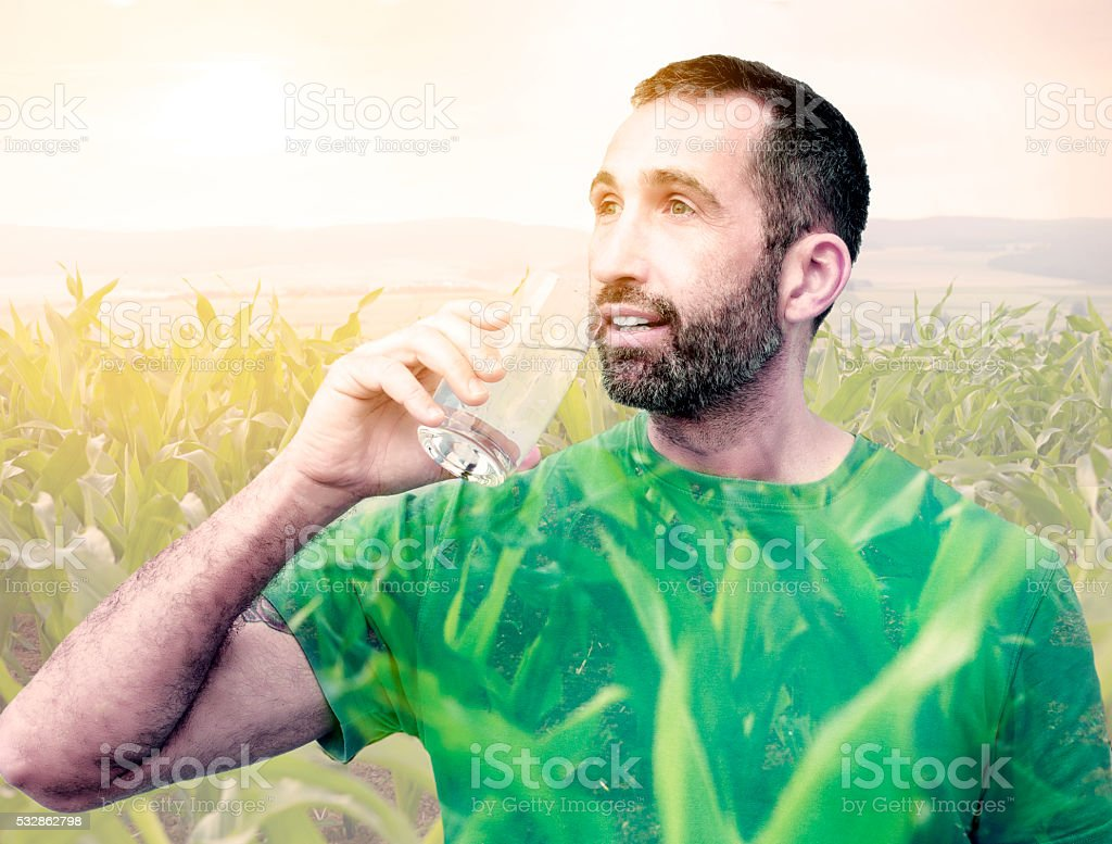 double exposure of man drinking water and field stock photo