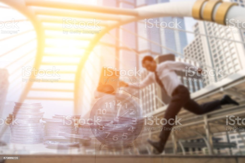 Double exposure of office workers go to work late and coins and alam clock in business concept stock photo