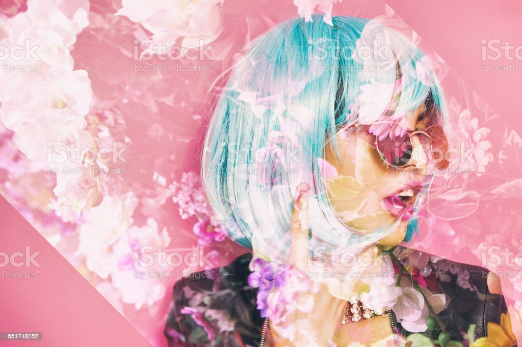 Double exposure of pop girl making the horns and flowers stock photo