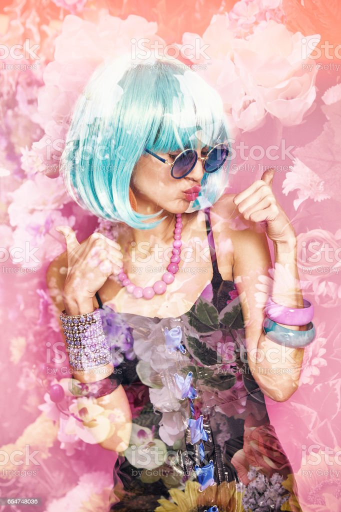 Double exposure of pop girl with thumbs up and flowers stock photo