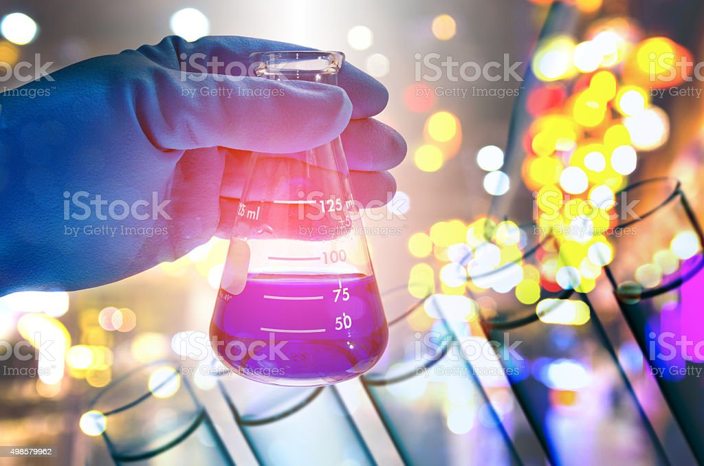 Double exposure of scientist hand holding laboratory flask stock photo