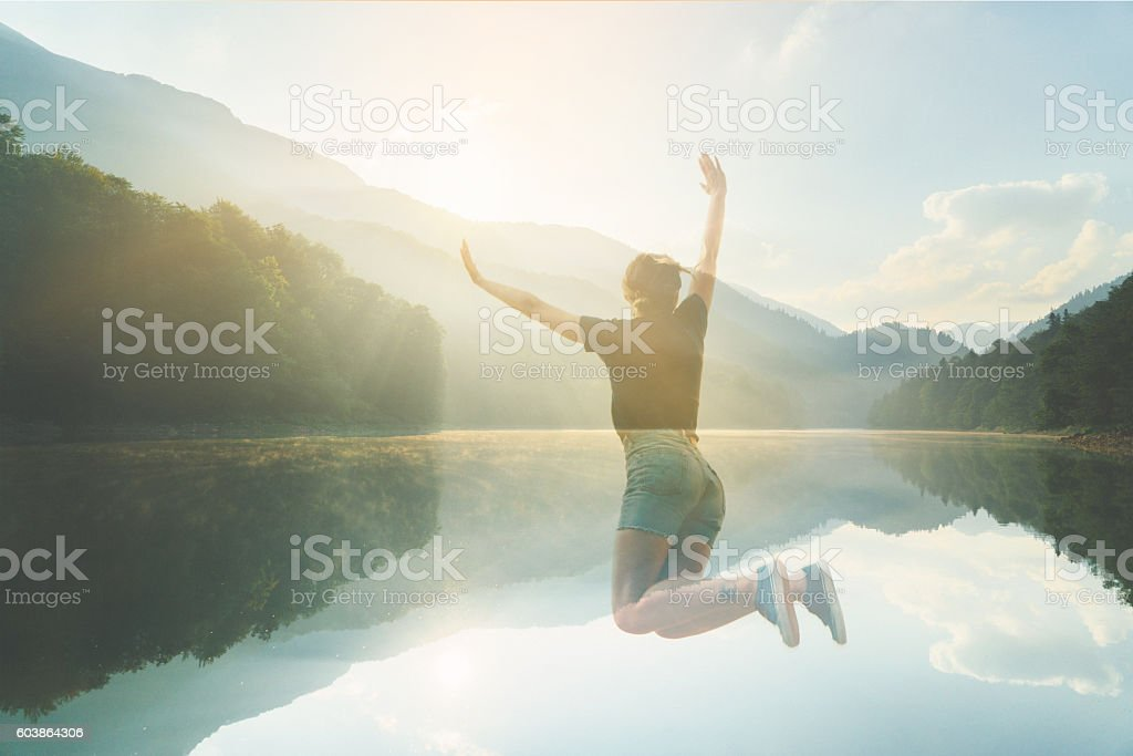 Double exposure of woman jumping and lake stock photo