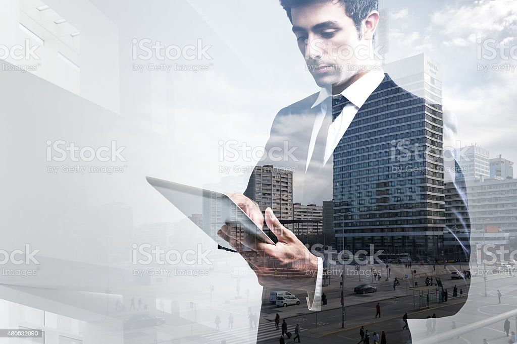 Double exposure of young Businessman Using Digital Tablet stock photo