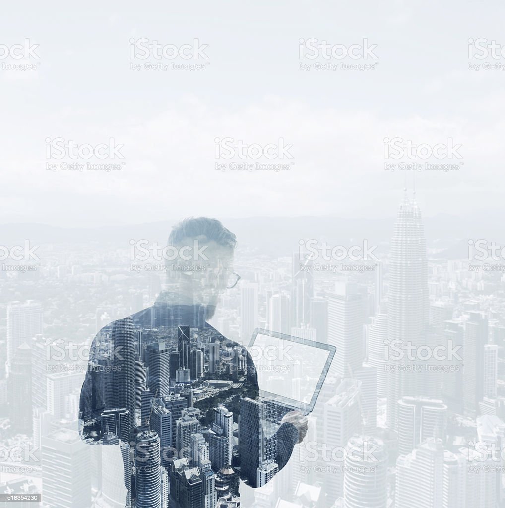 Double exposure young bearded businessman wearing black shirt holding contemporary stock photo