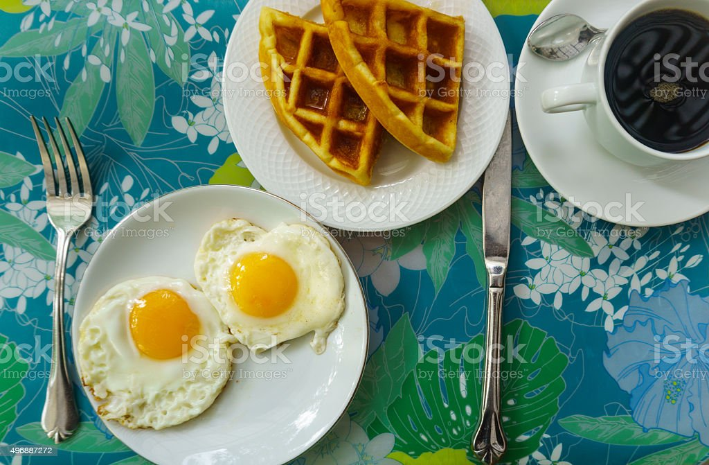 Double fried eggs, waffle, and coffee stock photo
