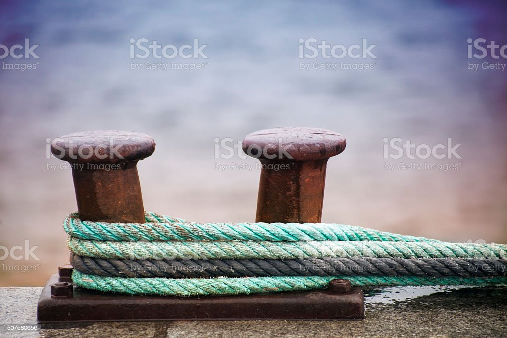 Double mooring post on stone dock and sea water. stock photo