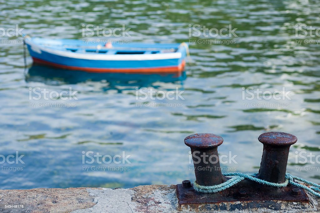 Double mooring post on stone dock, boat and sea water. stock photo