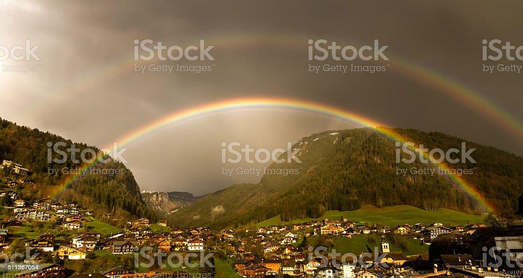 Double rainbow in a stormy sky, morzine Avoriaz mountain village stock photo