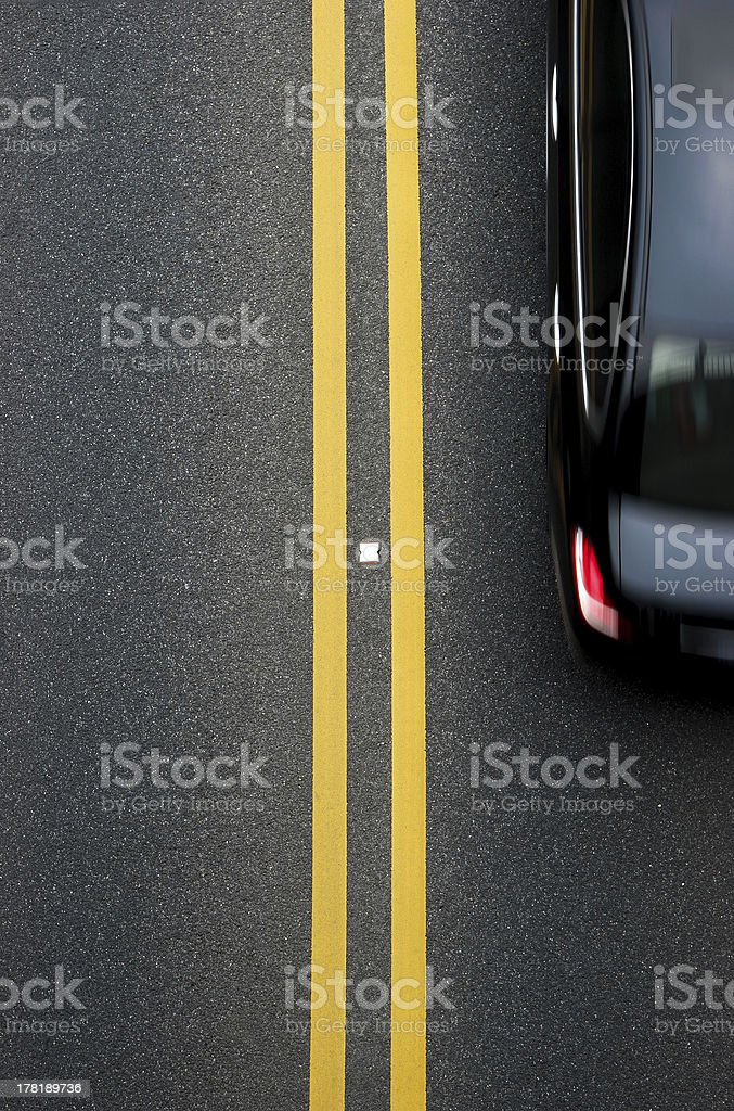 double yellow lines divider on blacktop with a car passing royalty-free stock photo