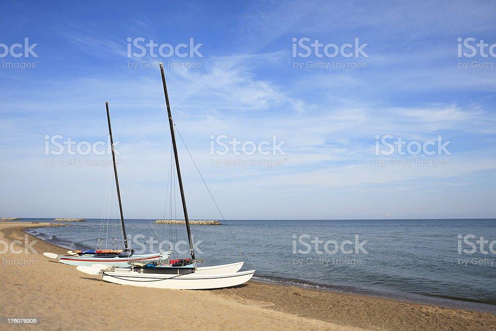 Double-hull sailing catamarans on wide swath of beach stock photo