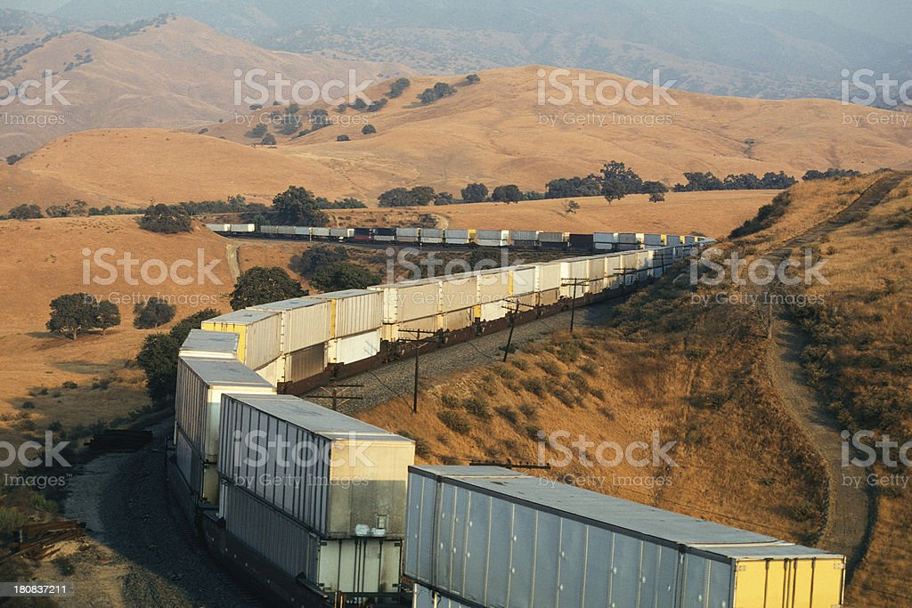 Double-stack white container train rounding hilly curves stock photo