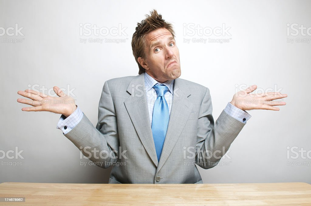 Doubtful Confused Office Worker Businessman Shrugs Shoulders at his Desk stock photo