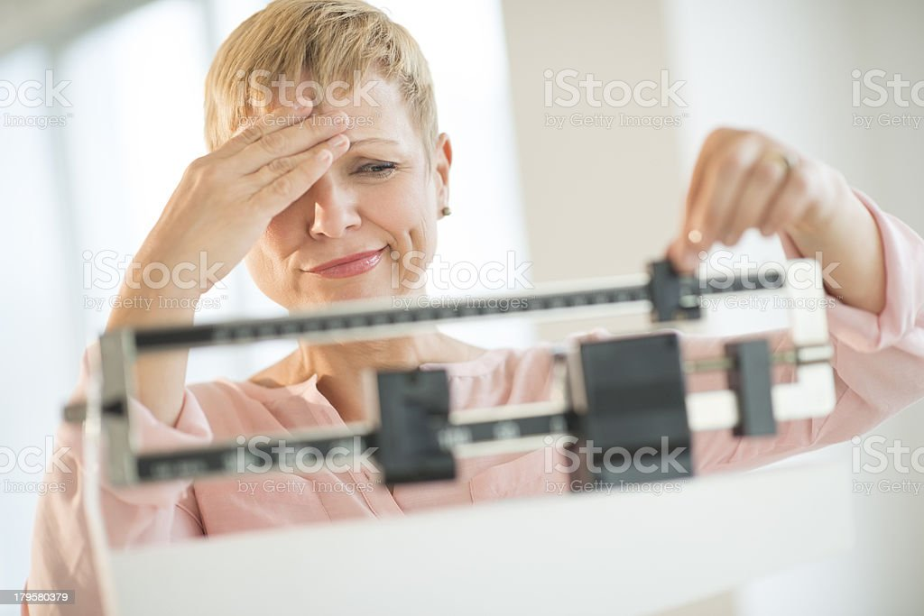 Doubtful Woman Adjusting Weight Scale stock photo
