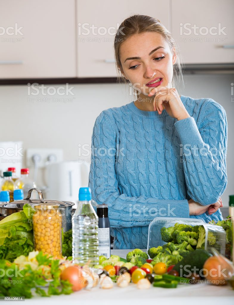 Doubting girl thinking what to cook for dinner stock photo
