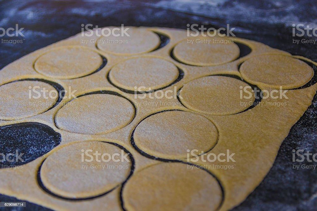 Dough for pasta tortellini or ravioli on the black table stock photo
