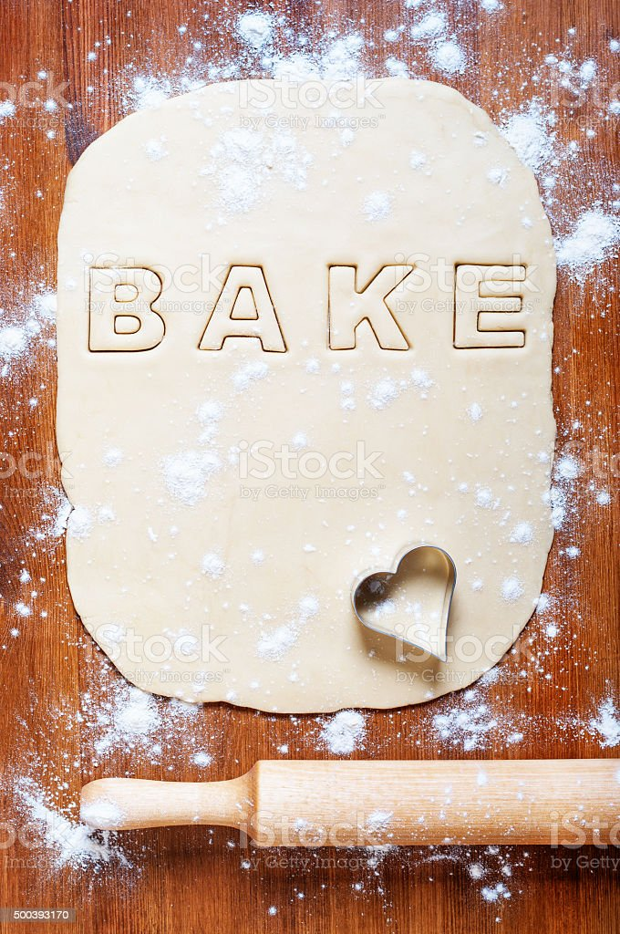 Dough with letters and rolling pin on the wooden table stock photo