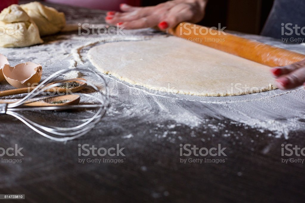 Dough with rolling pin on wooden table stock photo
