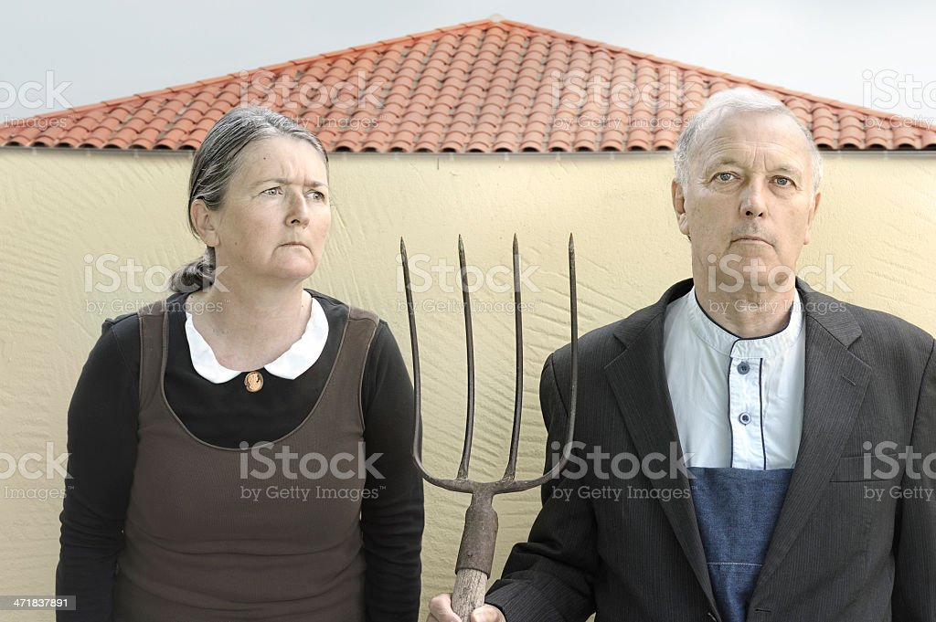 Dour rural couple with pitchfork stock photo