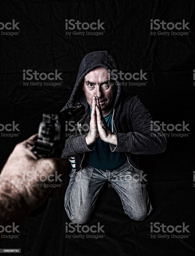 Down and out pleading on knees to gunman stock photo