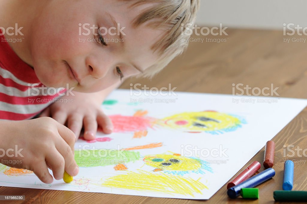 Down Syndrome boy drawing people on white paper with crayons stock photo