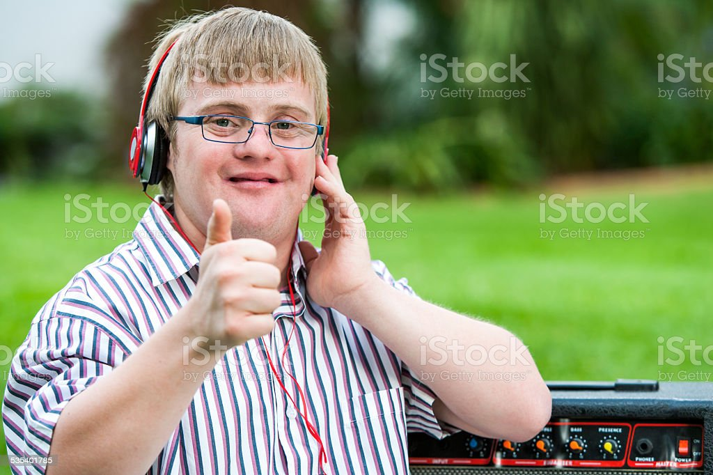 Down syndrome boy with headset doing thumbs up. stock photo