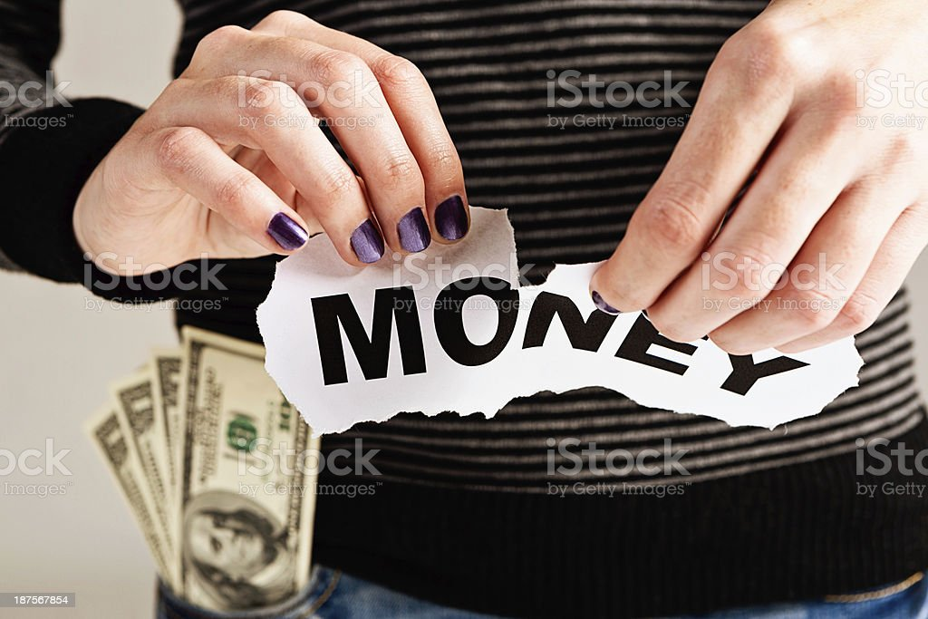 Down with money! Feminine hand tears up sign. royalty-free stock photo