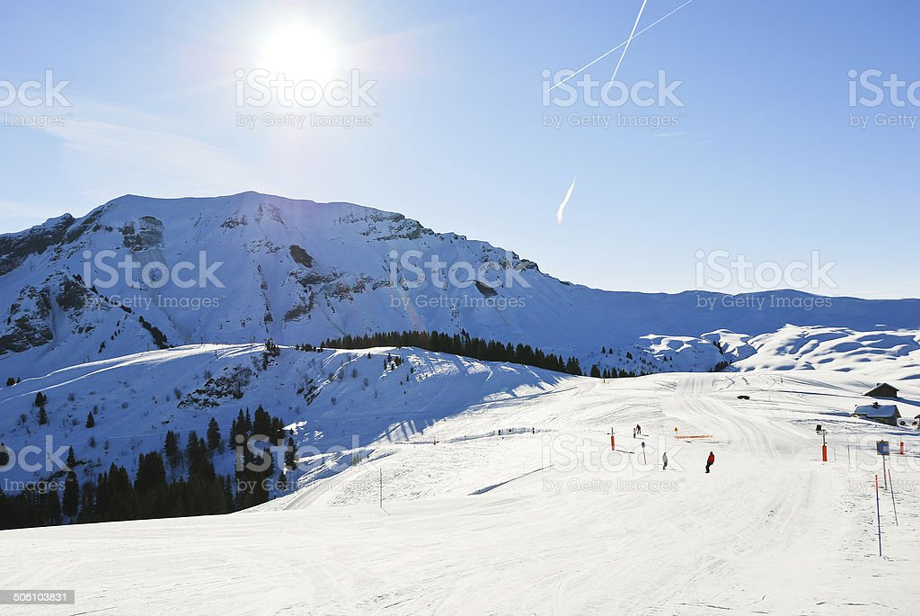 downhill skiing on snow slopes in sunny day stock photo