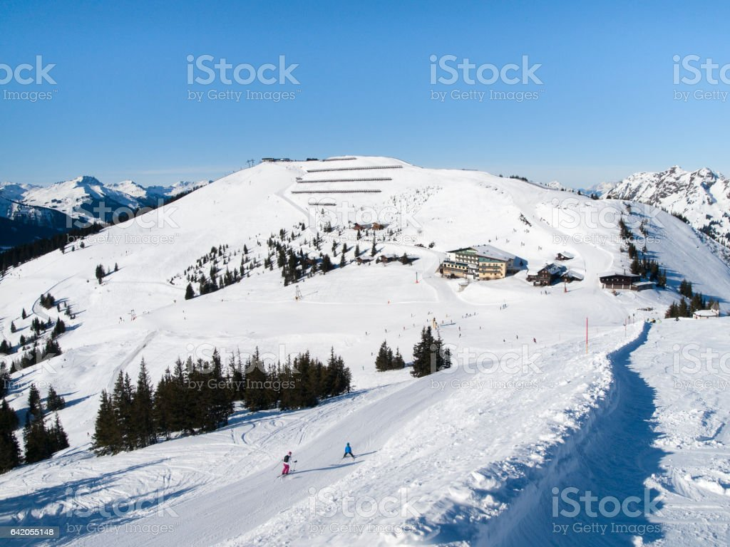 Downhill slope and apres ski mountain hut with restaurant terrace in Saalbach Hinterglemm Leogang winter resort, Tirol, Austria, Europe. Sunny day shot stock photo