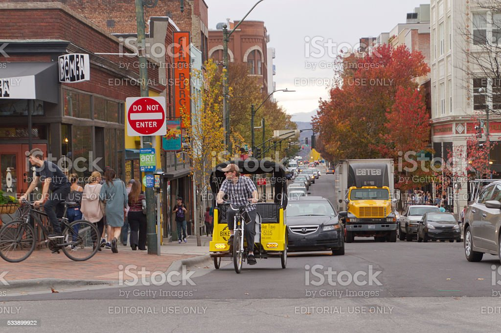 Downtown Asheville Street With Traffic and a Bike Taxi stock photo