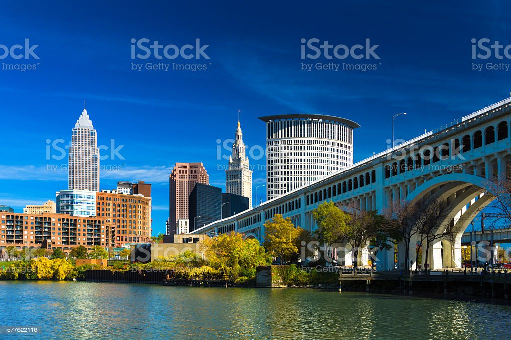 Downtown Cleveland with River, Bridge, Trees, and Deep Blue Sky stock photo