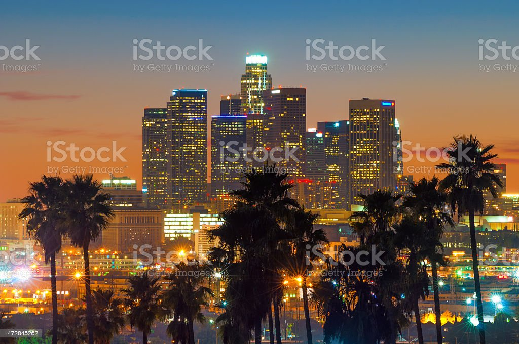 Downtown Los Angeles at sunset with palm tree silhouettes stock photo