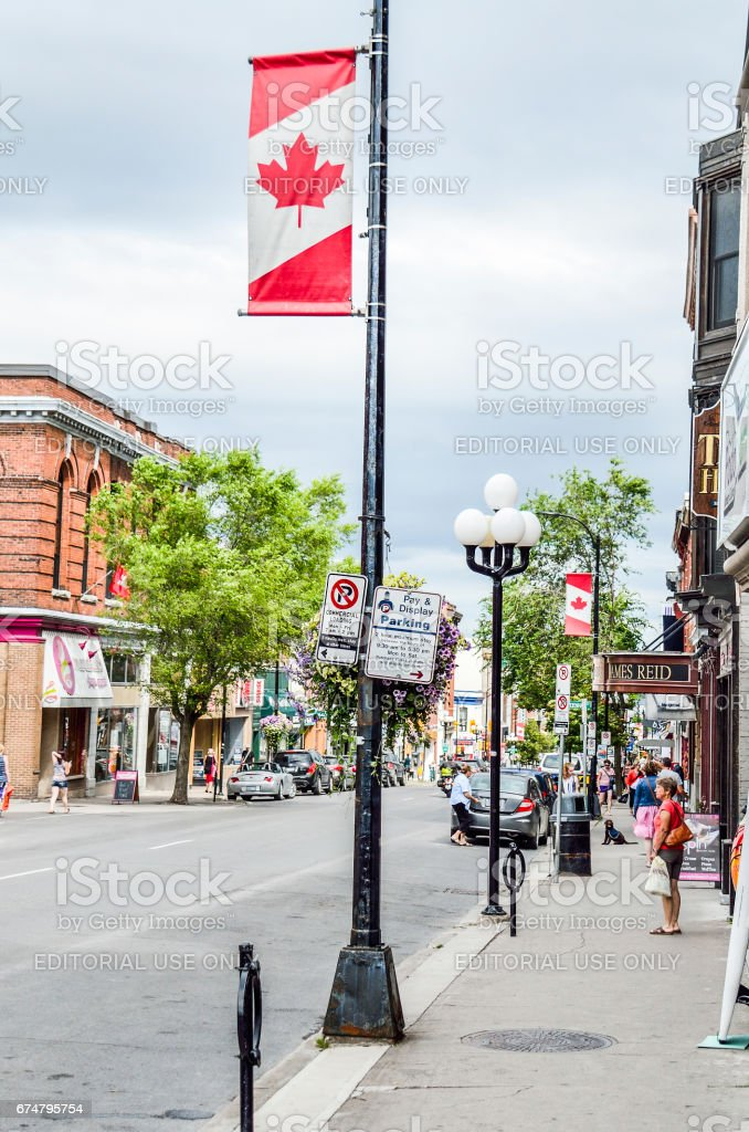 Downtown street with flag banner and people stock photo