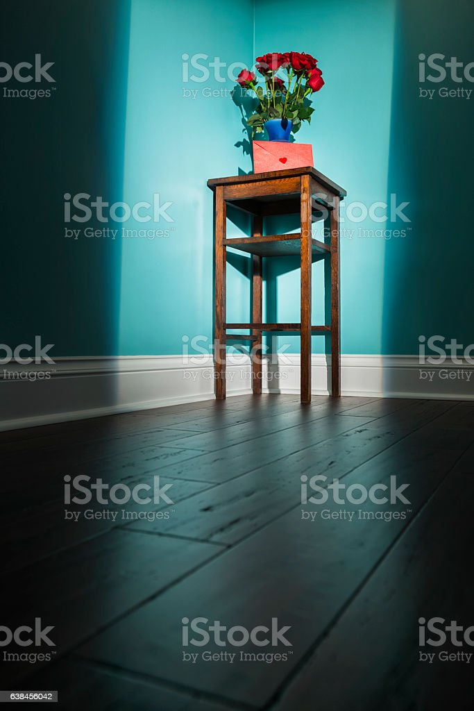 Dozen roses and card in shaft of light from door stock photo
